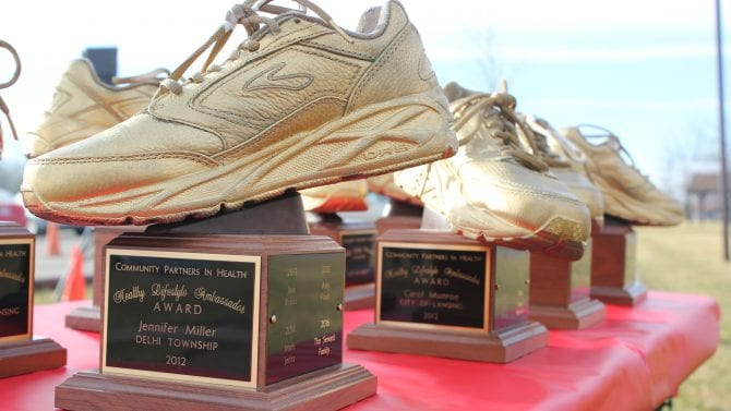 A gold painted tennis shoe award for healthy living on display