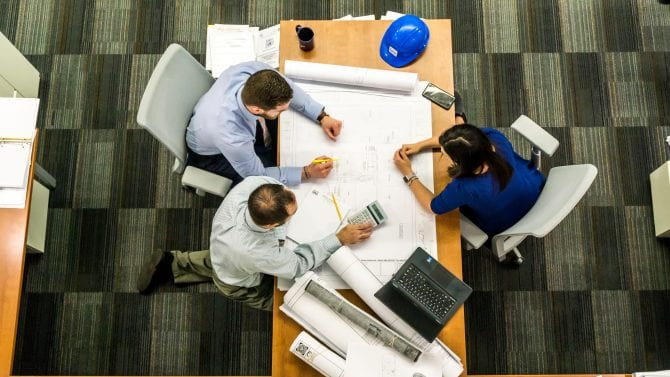 birds eye view of three people working at a table.