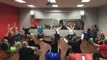 Image of Sally Miller working out with other Silver Sneakers members at Snap Fitness.