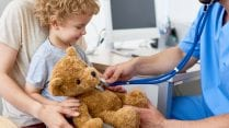 Image of doctor using stethoscope on teddy bear being held by toddler in his mother's lap.