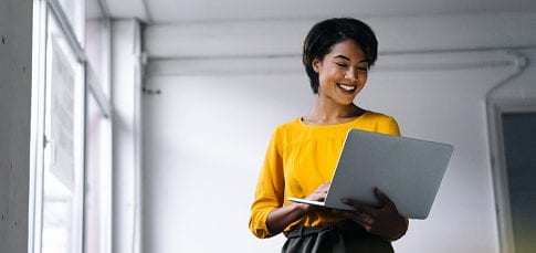 Smiling woman using laptop.