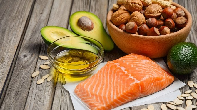 Selection of healthy fat sources salmon, cashews, olive oil. avocado