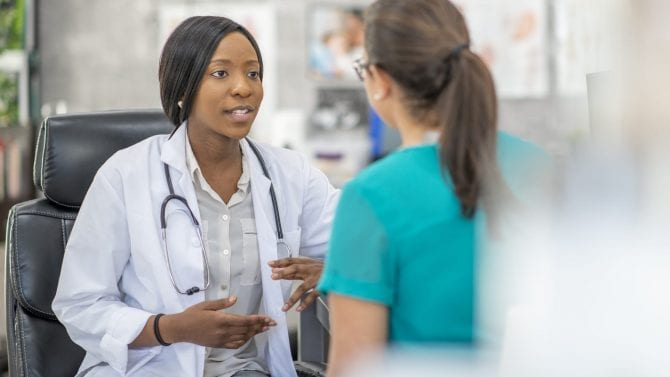 Female doctor speaks with female patient