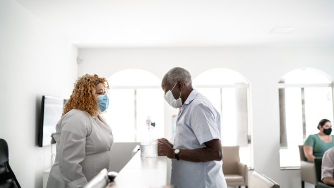 A medical clinic reception, receptionist talking to patient using face mask.