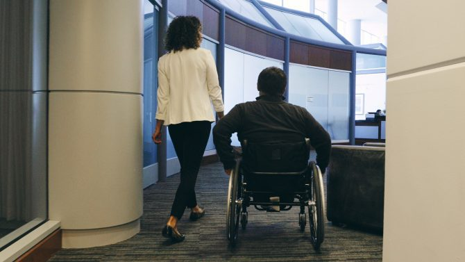 A person walks next to another person in a wheelchair in an office